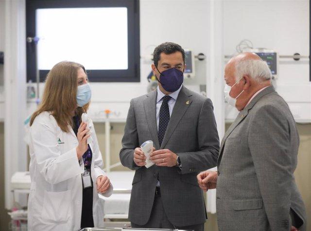 El presidente de la Junta de Andalucía, Juanma Moreno (c), en una visita al Hospital Macarena de Sevilla.