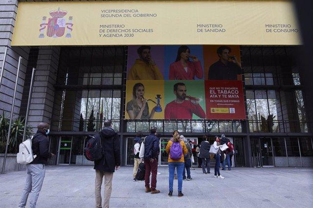 Varias personas hacen cola en el exterior del Ministerio de Sanidad para acceder al centro de examen de las pruebas de Formación Sanitaria Especializada (FSE), en Madrid (España), a 27 de marzo de 2021.