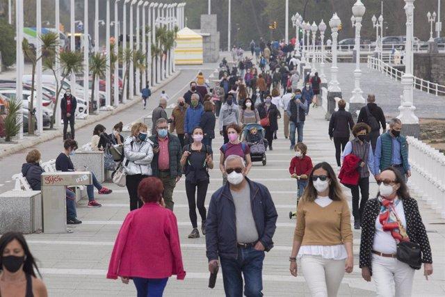 Varias personas caminan por el Paseo Marítimo de Gijón durante el primer día del puente de Semana Santa, en Gijón.