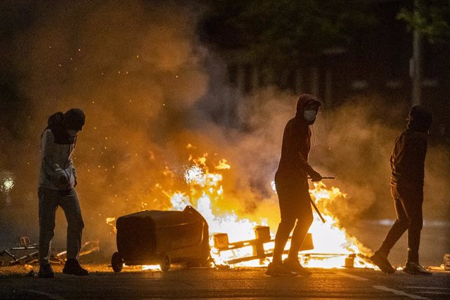 07 April 2021, United Kingdom, Belfast: People stand next to a fire during further unrest. Northern Ireland has had several consecutive nights of street violence and disorder in a number of mainly loyalist areas following a controversial decision last wee