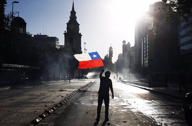 Archivo - 29 October 2019, Chile, Santiago: A demonstrator waves a Chilean flag during clashes following an anti-government protest. For the past two weeks, Chile has been experiencing a wave of strong protests that led to the replacement of eight ministe