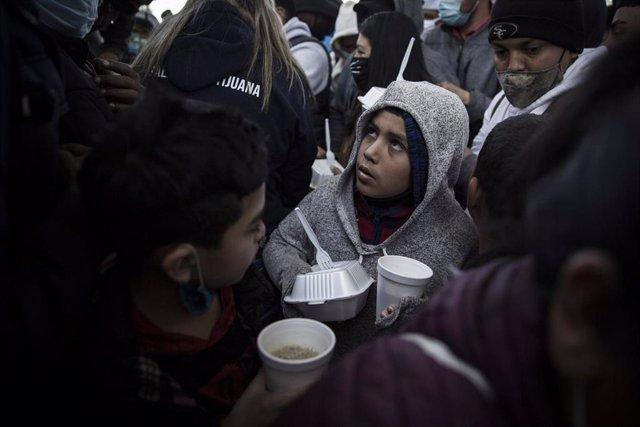 Archivo - Un niño migrante en la frontera entre México y Estados Unidos.