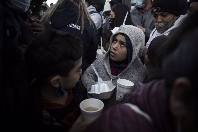 Archivo - 19 February 2021, Mexico, Tijuana: A migrant child receives a meal amid a crowd of awaiting asylum seekers at the El Chaparral between Mexico and the US. Starting from today, the new US administration under US President Joe Biden will gradually