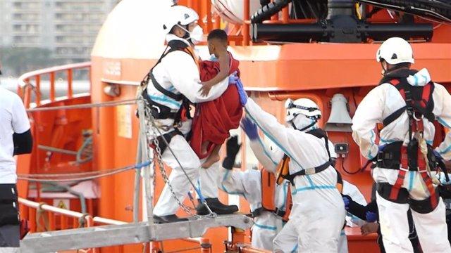 Un miembro de la Cruz Roja ayuda a bajar del barco a un niño migrante en el puerto de Arguineguín (Gran Canaria)