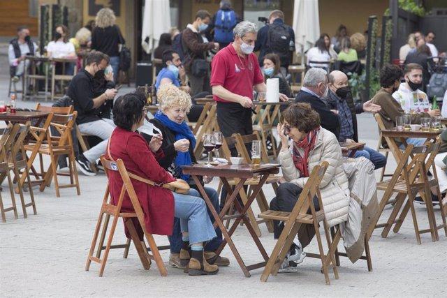 Una terraza llena de gente durante el primer día del puente de Semana Santa, en Gijón, Asturias (España).