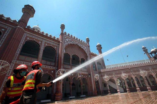 Archivo - Trabajos de desinfección en una mezquita de Pakistán durante la pandemia de coronavirus
