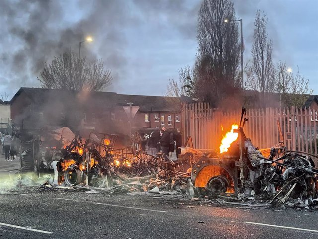 07 April 2021, United Kingdom, Belfast: Wreckage of a Metrobus still on fire during further unrest. Northern Ireland has had several consecutive nights of street violence and disorder in a number of mainly loyalist areas following a controversial decision