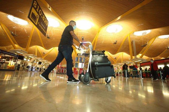 Un hombre camina con varias maletas en un carro en la terminal T4 del Aeropuerto Adolfo Suárez Madrid-Barajas,