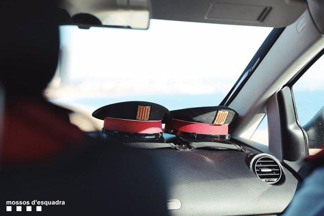 Archivo - Dos gorras en un vehículo de Mossos d'Esquadra (ARCHIVO)