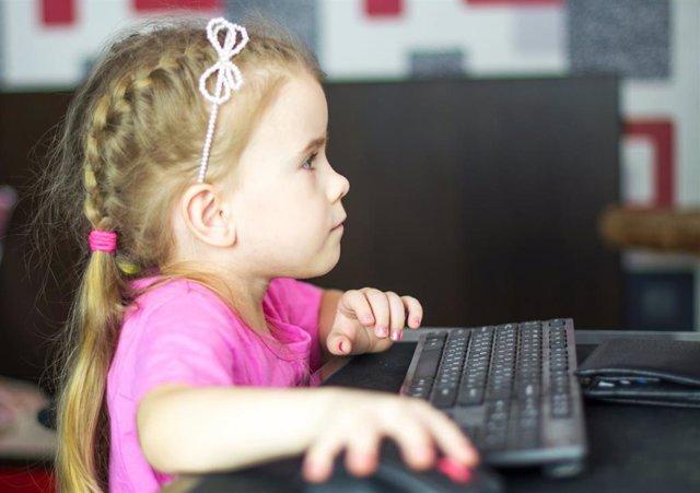 Una niña utilizando un ordenador de sobremesa