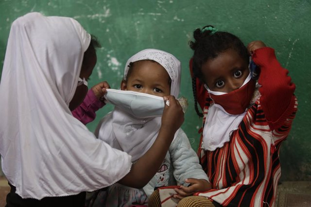 Una mujer le pone la mascarilla a un par de niños.
