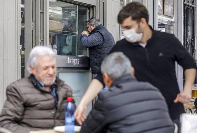 Archivo - Arxiu - Un cambrer serveix a dos clients en una terrassa el primer dia de l'obertura de l'hoteleria a València
