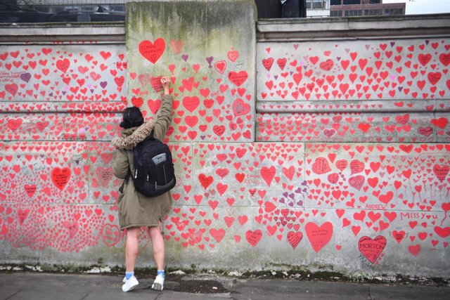 08 April 2021, United Kingdom, London: A woman draws a heart on the National Covid Memorial Wall which commemorates people who died in the UK from coronavirus. Photo: Victoria Jones/PA Wire/dpa