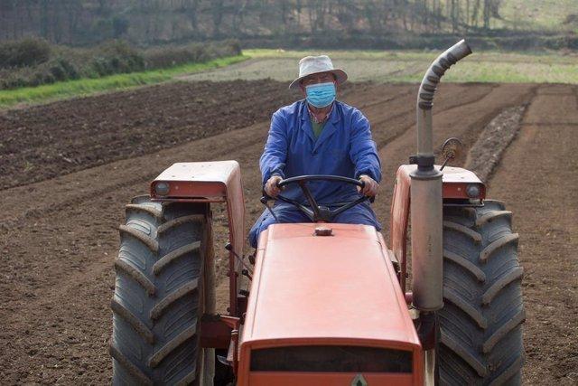 Un tractorista ara sus tierras