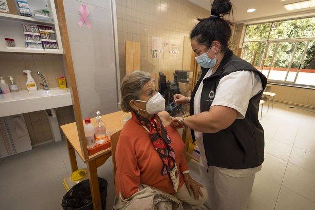 Una sanitaria vacuna a una mujer mayor de 80 años con la dosis de Pfizer en el ambulatorio Virgen Peregrina, en Pontevedra,