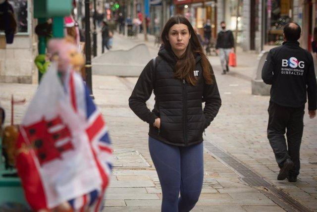 Una chica camina sin mascarilla por Gibraltar.