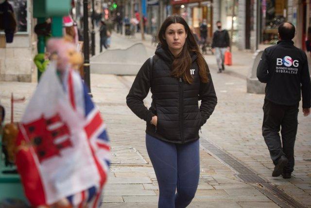 Una chica camina sin mascarilla por Magín atrévete, Gibraltar. ,después de que España haya decidido levantar la restricción temporal del acceso por vía terrestre al espacio Schengen a través del puesto de control de personas con el territorio de Gibraltar