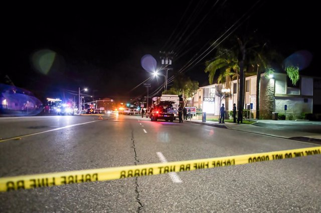 31 March 2021, US, Orange: Police tape cordons off the crime scene where four people, including a child, were killed after a shooting occurred in a business building in Orange On Wednesday evening. This is the third mass shooting incident in the United St