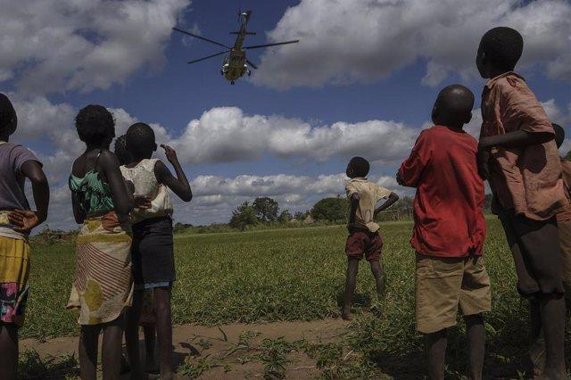 Archivo - Un grupo de niños observa un helicóptero en Mozambique