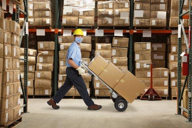 Archivo - Un trabajador del almacén con una máscara protectora y un casco empuja una carretilla de mano y una pila de cajas en un almacén lleno de inventario.