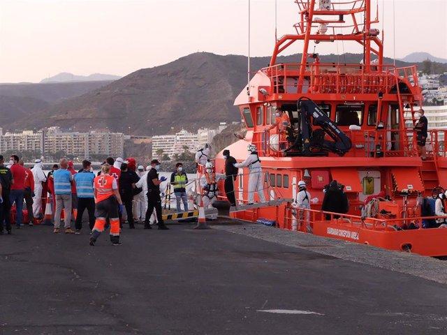MIembros de la Cruz Roja ayudan a bajar del barco a migrantes en el puerto de Arguineguín (Gran Canaria)