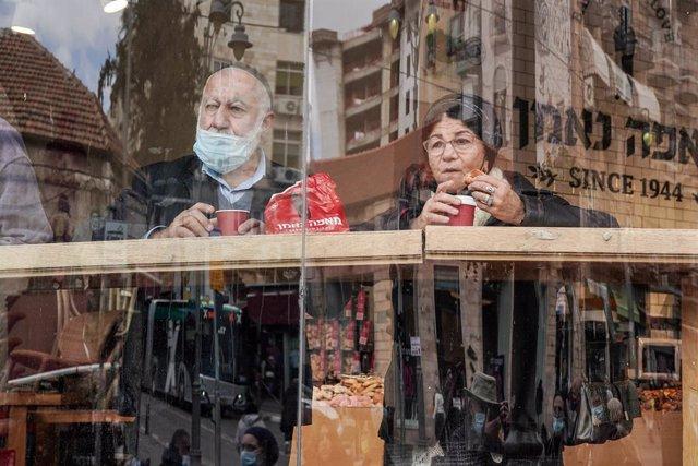 Archivo - Dos personas toman un café en Jerusalén durante la pandemia.