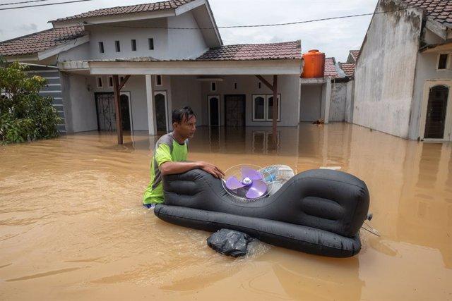Residentes de Pekanbaru intentan salvar sus pertenencias tras un fuerte ciclón.