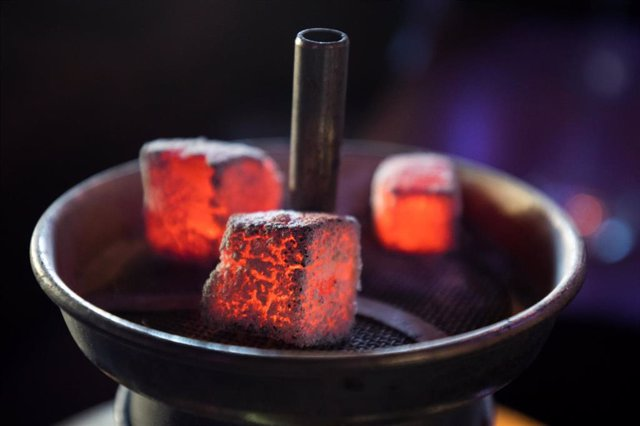 Archivo - 11 February 2019, Hamburg: Glowing coal lies on a metal screen above the tobacco in the head of a water pipe in a shisha bar. The operators of shisha bars in Hamburg are to be obliged by law to protect their guests from carbon monoxide poisoning