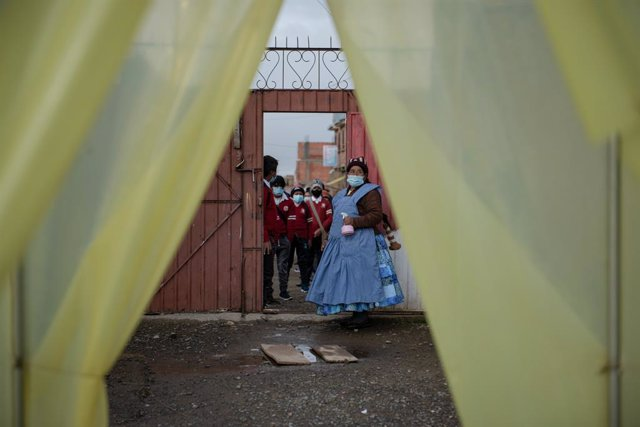 Archivo - 11 February 2021, Bolivia, Palcoco: Students wear face masks line up at the entrance of the Bolivian-Japanese school where they are sprayed by the facility's staff against the spread of the coronavirus. The school has been allowed to provide par