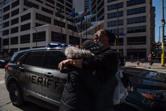 02 April 2021, US, Minneapolis: Protesters cry while police officers removing the photos and locks from the fencing outside the Hennepin County Courthouse, where the trial of a former Minneapolis police officer Derek Chauvin in the death of George Floyd t