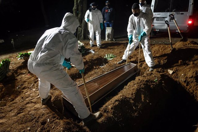 02 April 2021, Brazil, Sao Paulo: Employees of the Vila Formosa cemetery, the largest in Latin America, carry a coffin to bury a person who died of coronavirus (Covid-19). Due to the high number of deaths, the employees also work during the night. Photo: