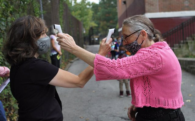 Archivo - 29 September 2020, US, New York: Teacher Marissa Maher (L) and parent Coordinator Nina Velasquez check each other temperature on the first day of school. New York City elementary schools welcomed students back to the classroom on Tuesday, while