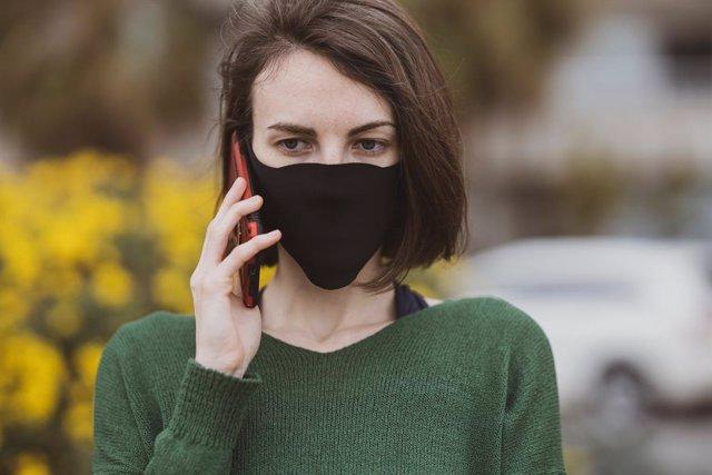 Mujer con máscarilla usando el móvil
