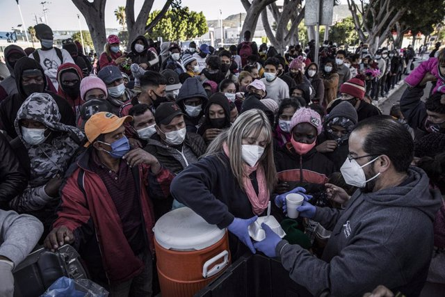 Archivo - 19 February 2021, Mexico, Tijuana: Food and water are distributed to waiting asylum seekers at the El Chaparral between Mexico and the US. Starting from today, the new US administration under US President Joe Biden will gradually allow the entry