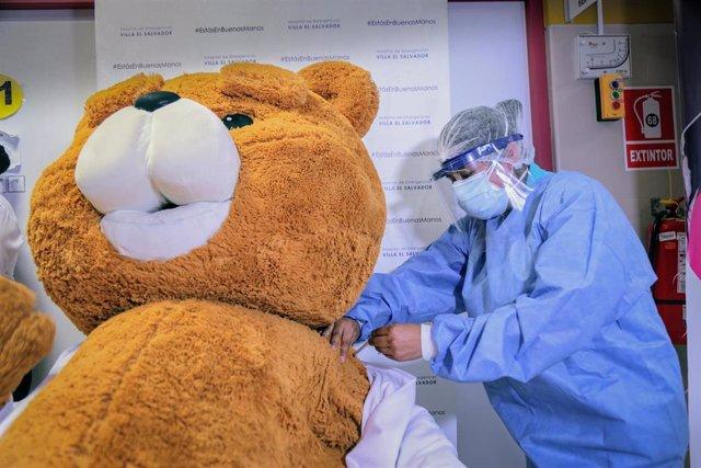 Archivo - Una persona disfrazada de oso de peluche recibe simbólicamente la vacuna del coronavirus en Lima, Perú