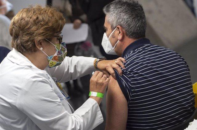 Una trabajadora sanitaria administra la primera dosis de la vacuna AstraZeneca contra el Covid-19 a una persona en el Wizink Center, a 9 de abril de 2021, en Madrid, (España).