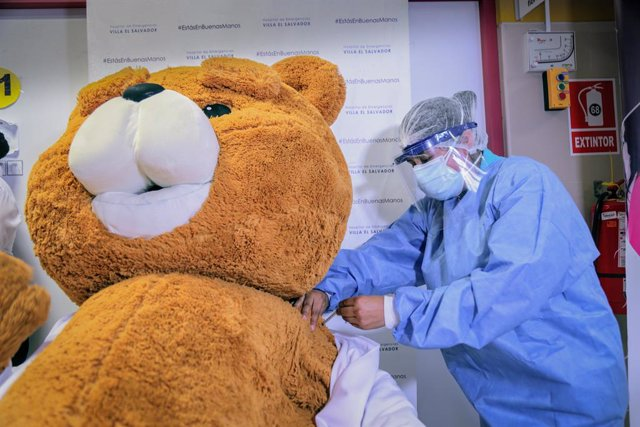 Archivo - HANDOUT - 10 February 2021, Peru, Lima: A person dressed as a bear is symbolically receiving a vaccination against Covid-19 at the Villa El Salvador Emergency Hospital during a vaccination campaign for health care workers who work in intensive c