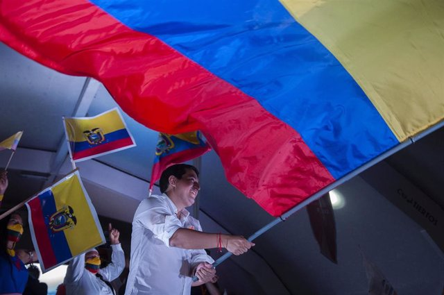 08 April 2021, Ecuador, Quito: Andres Arauz, the presidential candidate in Ecuador, waves a large national flag on stage at the end of his campaign. The runoff between leftist candidate Arauz and conservative banker Lasso is scheduled to take place on 11