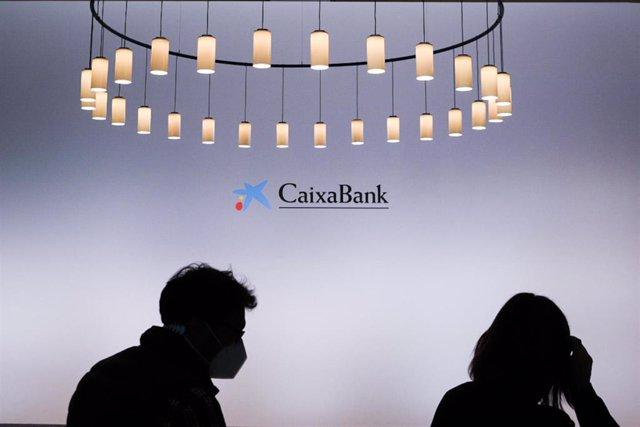 Dos personas a su llegada a una reunión del nuevo Consejo de Administración de CaixaBank, en Valencia, Comunidad Valenciana, (España), a 30 de marzo de 2021. El encuentro se produce tras el cierre de la fusión con Bankia el pasado 26 de marzo.