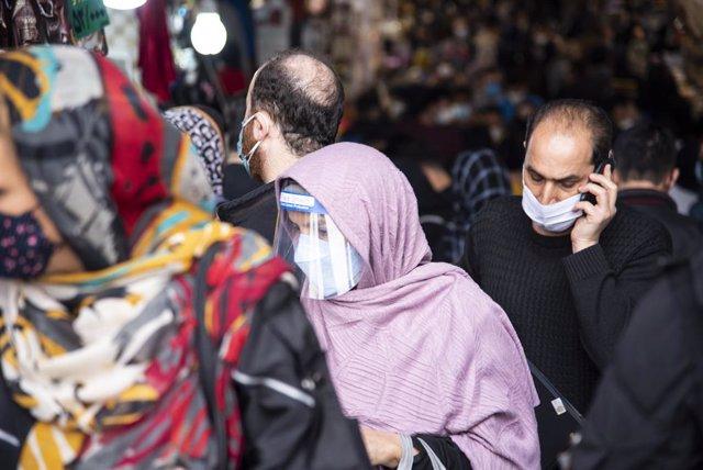 Archivo - Una mujer camina por la calle con mascarilla y pantalla facial en Teherán.