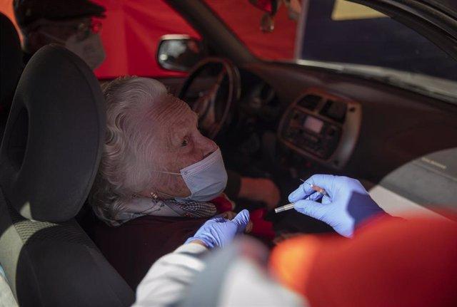 Archivo - Una mujer mayor de 90 años recibe la vacuna de Pfizer contra la Covid-19, en una carpa habilitada en la explanada del centro de salud del municipio Lora del Río.