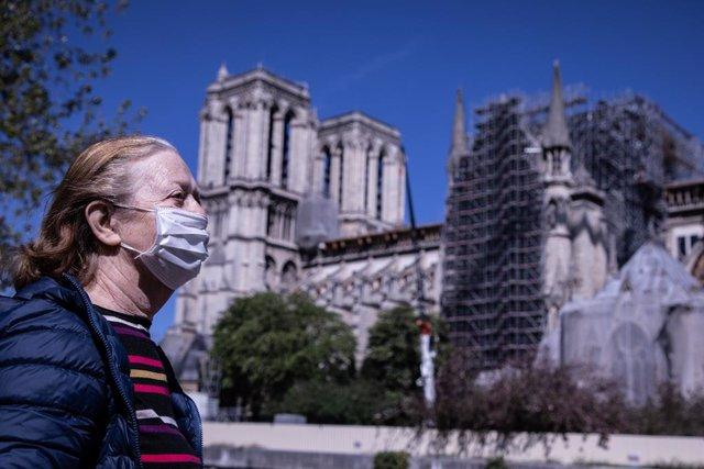 Archivo - Mujer con mascarilla cerca de la catedral de Notre Dame de París