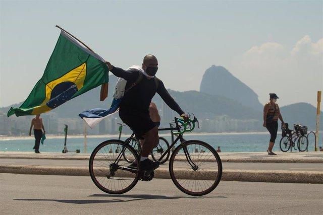 Una persona en bicicleta, con mascarilla y la bandera de Brasil en Río de Janeiro.