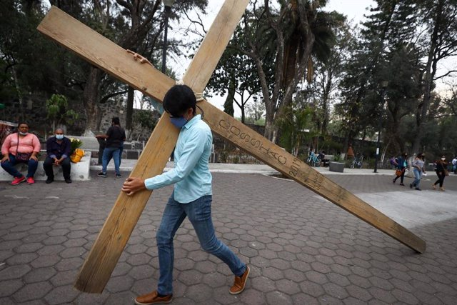 14 March 2021, Mexico, Mexico City: A man carries a big wooden cross at the church of La Cuevita during the first rehearsal with the cast of the Passion of Christ play which will be broadcasted on the internet for Holy Week due to the coronavirus (Covid-1