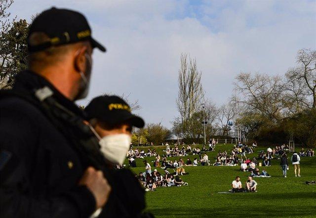 01 April 2021, Czech Republic, Prague: Police officers patrol Rieger Park, where people are enjoying the spring-like weather. Photo: Vondrou? Roman/CTK/dpa