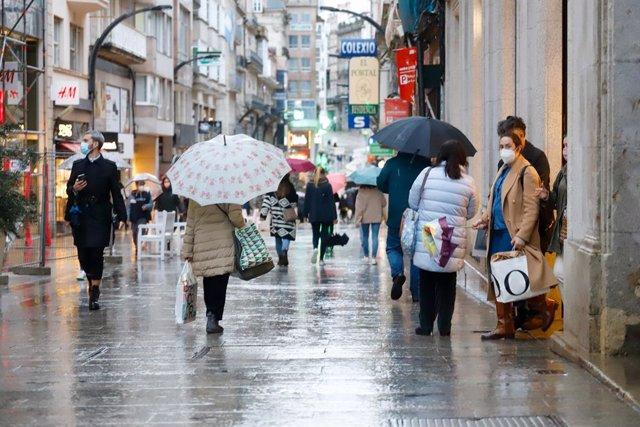 Archivo - Varias personas pasean en una calle comercial en una jornada marcada por el inicio de la entrada en vigor de una desescalada gradual en la región, en Vigo, Galicia (España), a 17 de febrero de 2021. Galicia reabre hoy cines, teatros, auditorios,