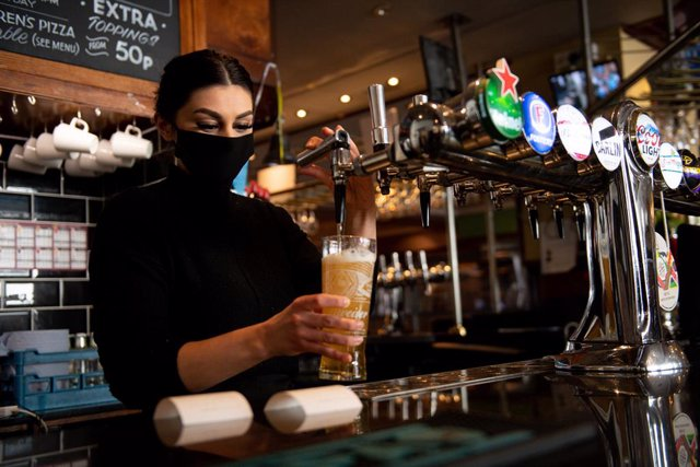 12 April 2021, United Kingdom, Birmingham: A waitress at the Figure of Eight pub pours a glass of beer. Shops, hairdressers and outdoor restaurants are now allowed to reopen following the easing of the coronavirus restrictions across England. Photo: Jacob