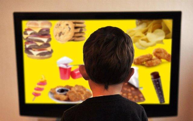 Archivo - Niño frente al televisor, comida no saludable, bollos