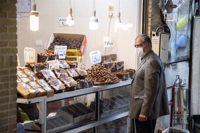 Un hombre con mascarilla ante una tienda en Qom, Irán