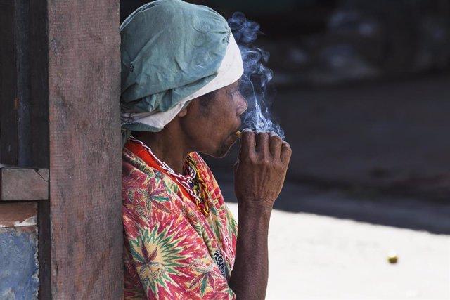 Una mujer fumando en un mercado local de Wamena, provincia de Papua, en Indonesia.